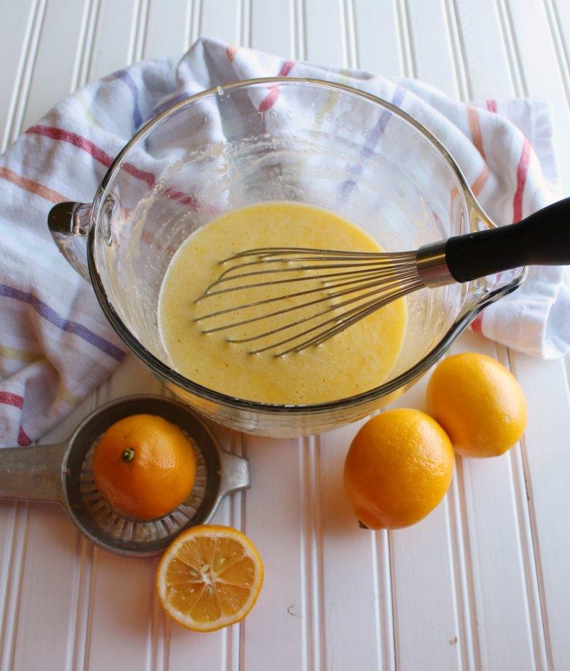 squeezing fresh lemons to make lemon bar filling.