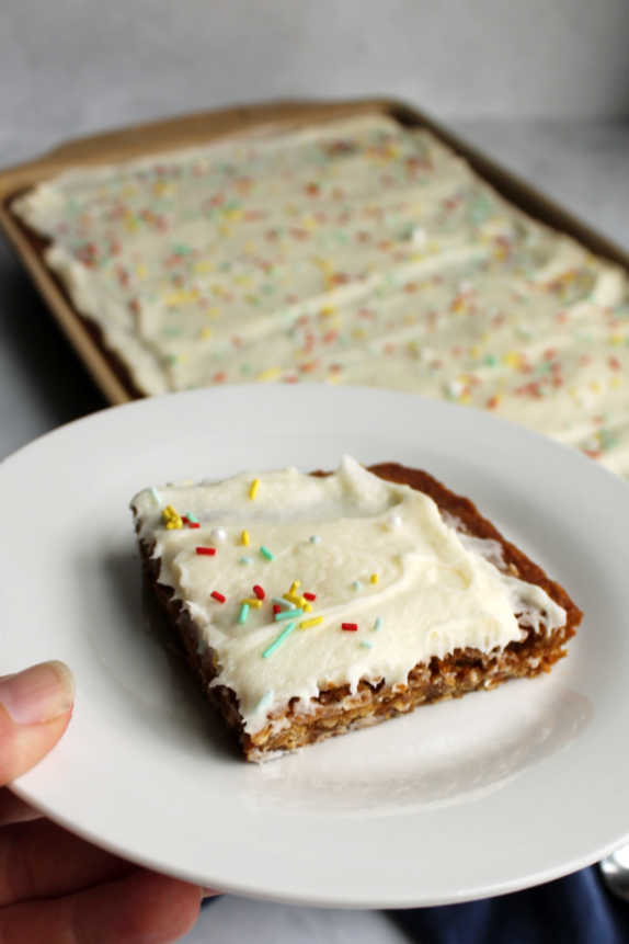 Marshmallow frosting spread over chewy oatmeal cookie bar
