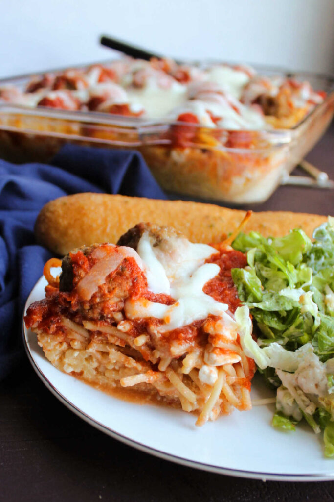 Piece of cheesy spaghetti casserole with tomato sauce and meatballs on top.
