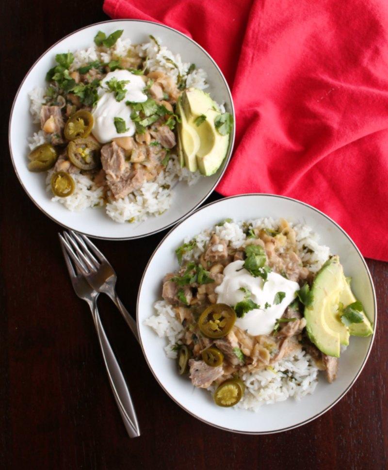 salsa verde pork burrito bowls with sour cream, jalapenos, cilantro and slices of avocado.