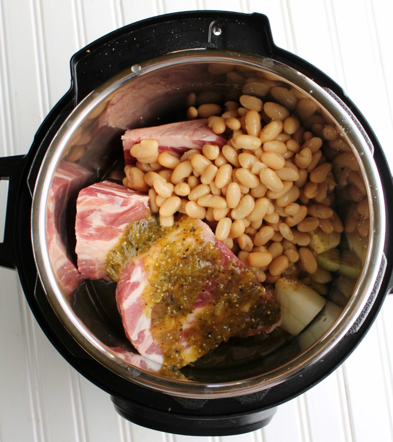 chunks of pork, beans, onions and salsa verde in instant pot ready to cook.