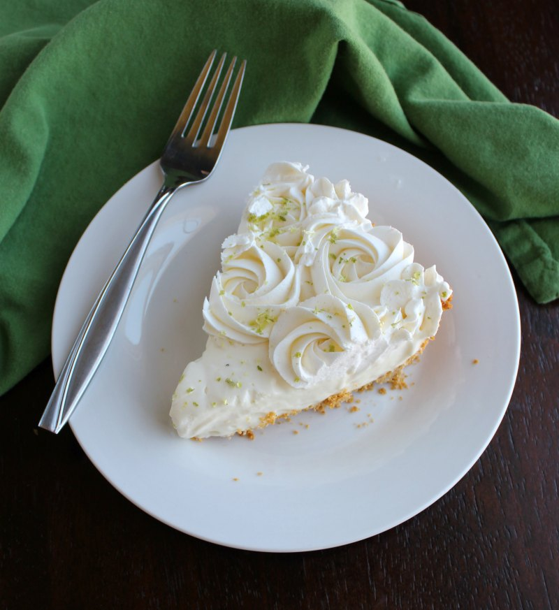 slice of key lime pie with whipped cream rosettes piped on it on plate with fork