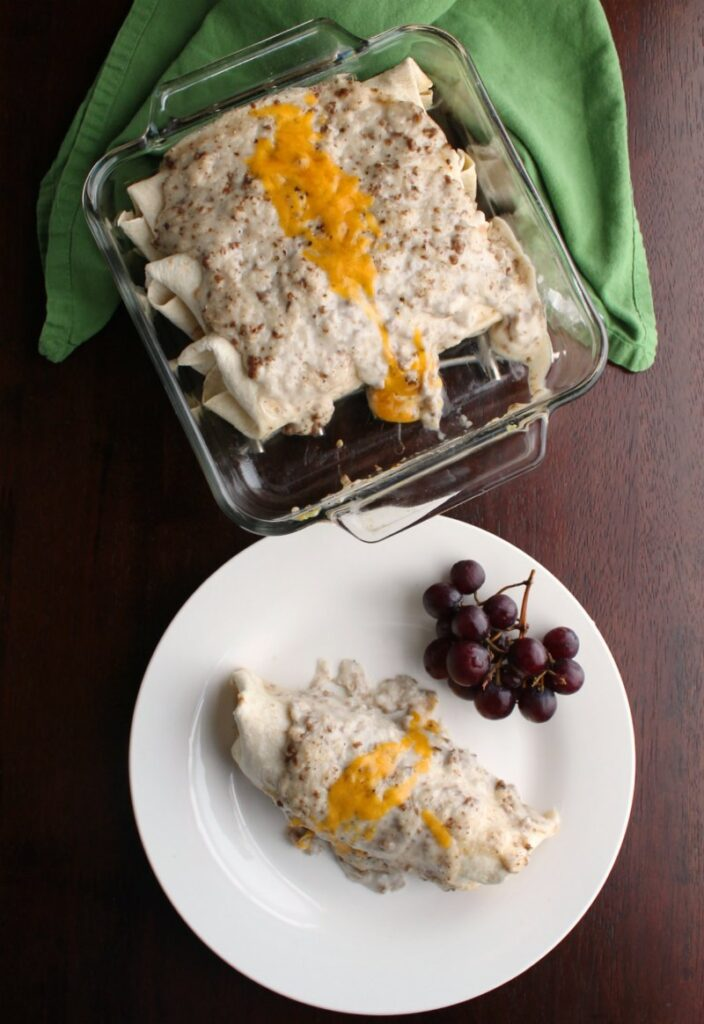 pan of smothered breakfast enchiladas with first one served on a plate with grapes.