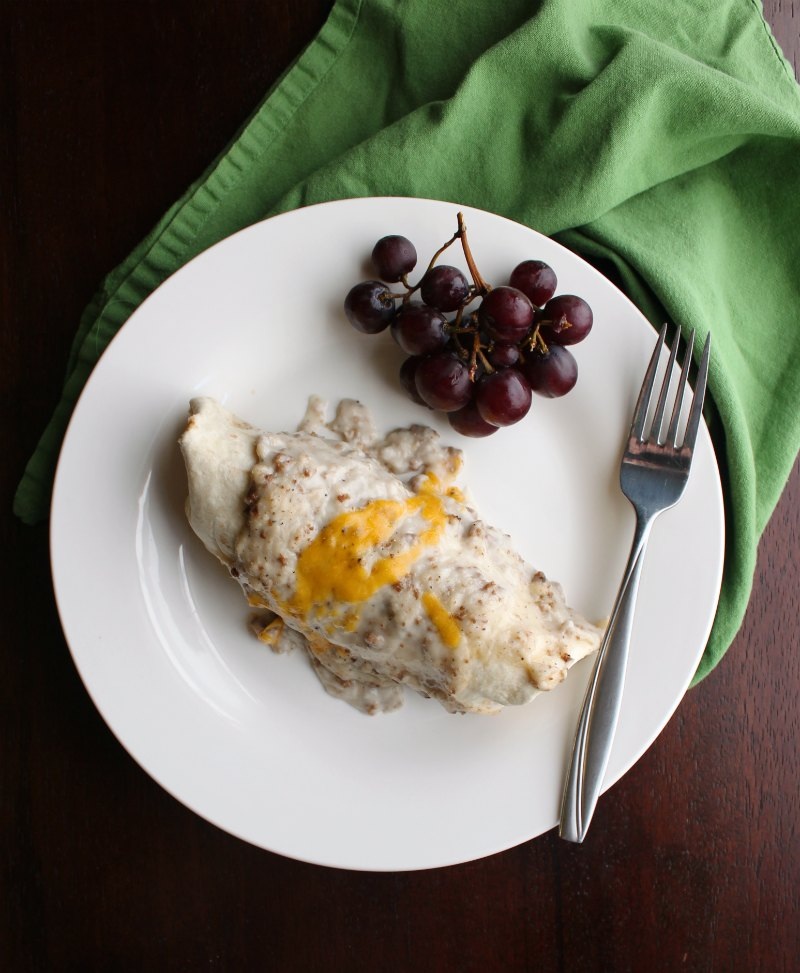 plate with smothered breakfast burrito fork and grapes.