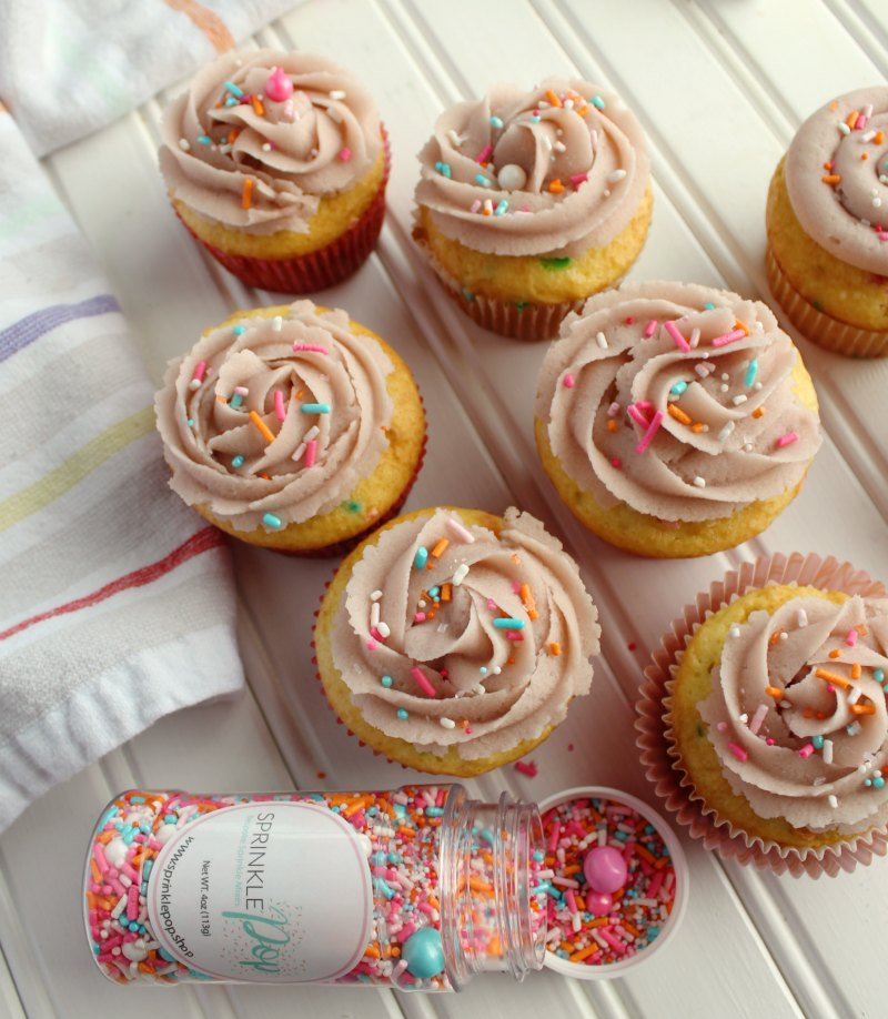 cupcakes with swirls of sugar cookie dough frosting and a bottle of springy sprinkles.