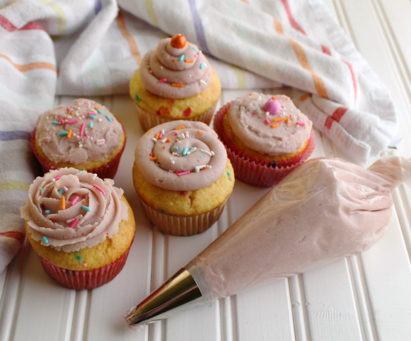 cupcakes with a variety of frosting decoration styles and piping bag.