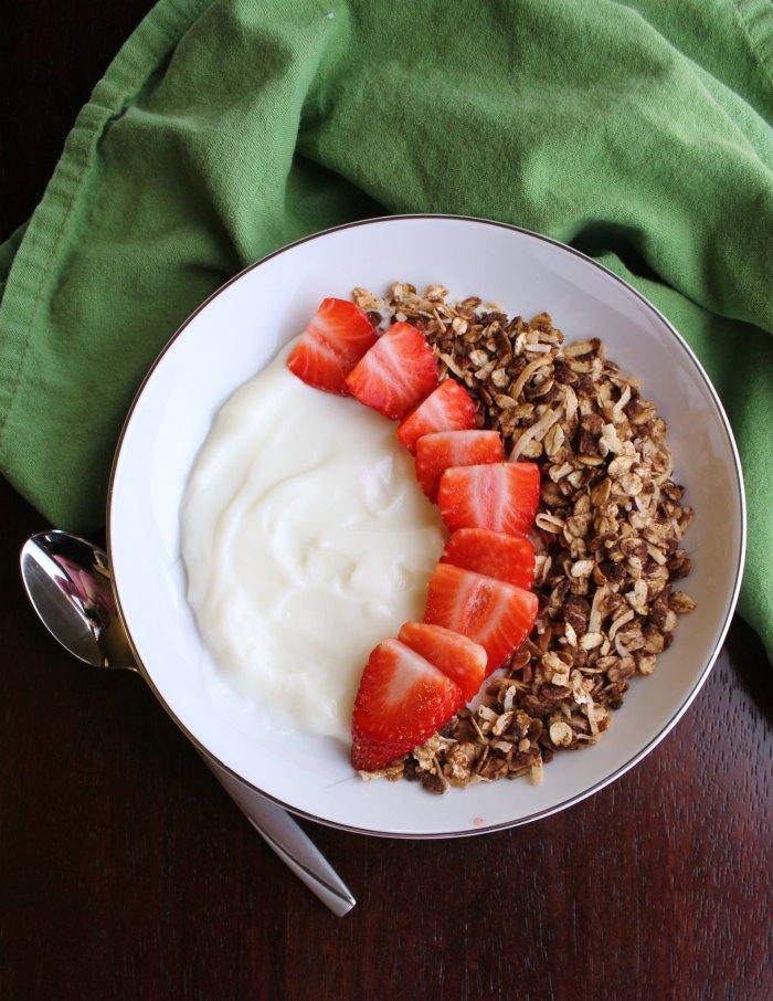 top view of bowl of yogurt with strawberries and chocolate granola.