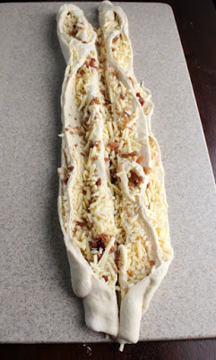 rolled bread dough cut in half down the length of the dough exposing the filling