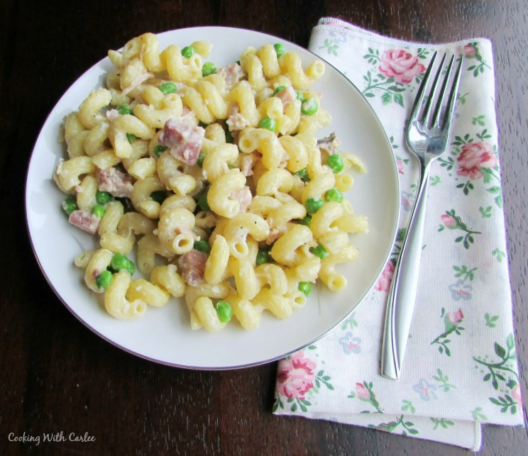 pate full of pasta with ham peas and cream with a fork and flowery napkin.
