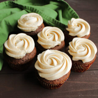 chocolate cupcakes topped with rosettes of light tan caramel buttercream ready to eat.