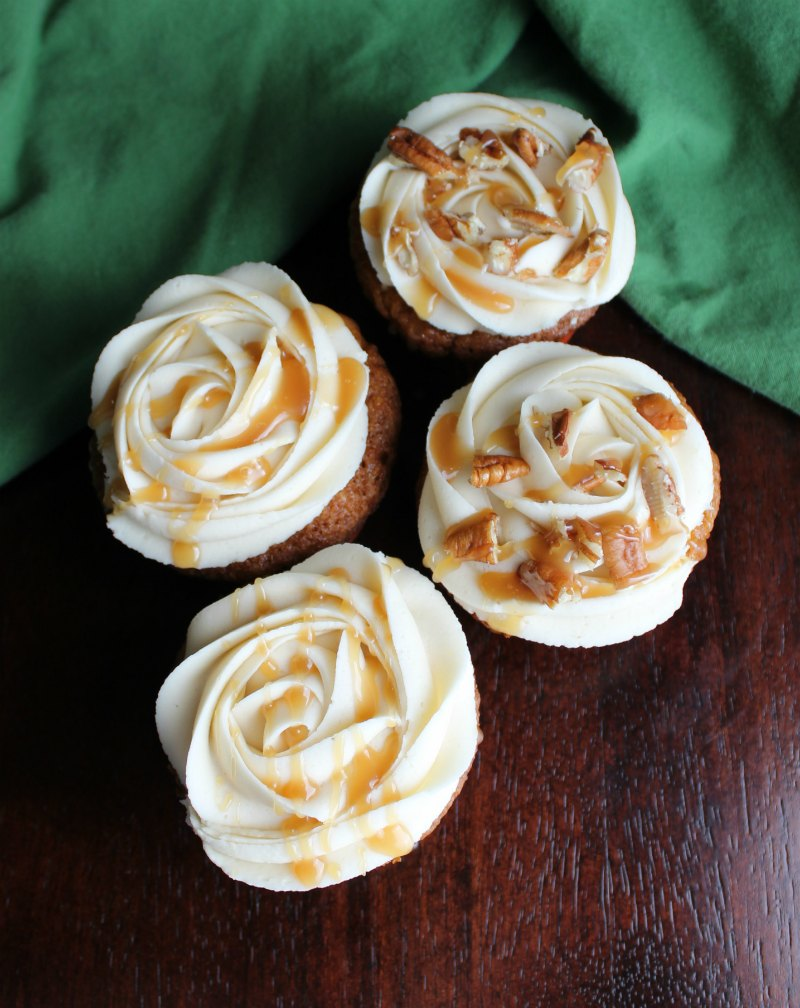 caramel buttercream on cupcakes with a caramel drizzle and pecan bits.