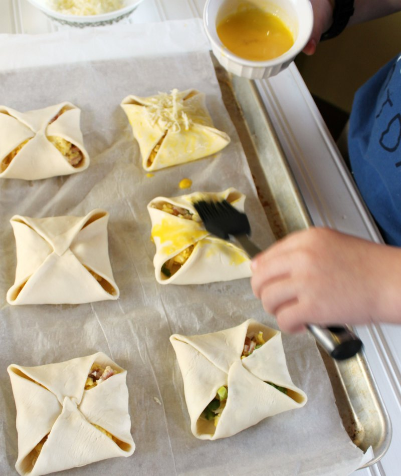 Little Dude brushing hand pies with egg yolk wash and topping with cheese.