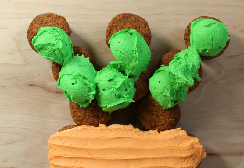 scoops of green frosting on the top of carrot cupcake cake, ready to be spread out.