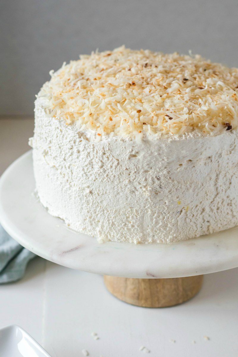 Round layer cake with fluffy white frosting and toasted coconut on top on cake stand.