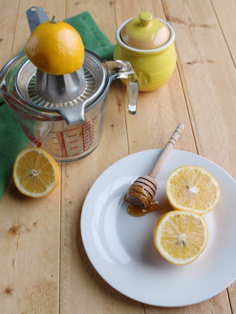 lemon half on juicer, lemons and honey pot all ready to be made into lemonade.