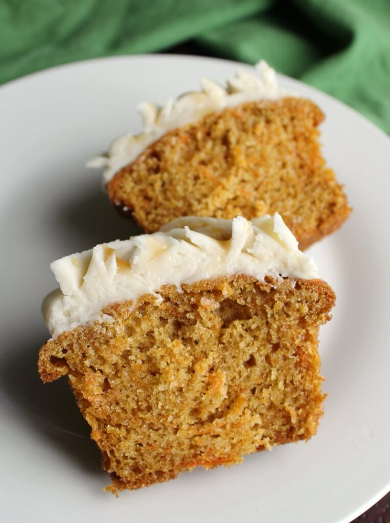 carrot cake cupcake cut in half with moist inside texture showing.