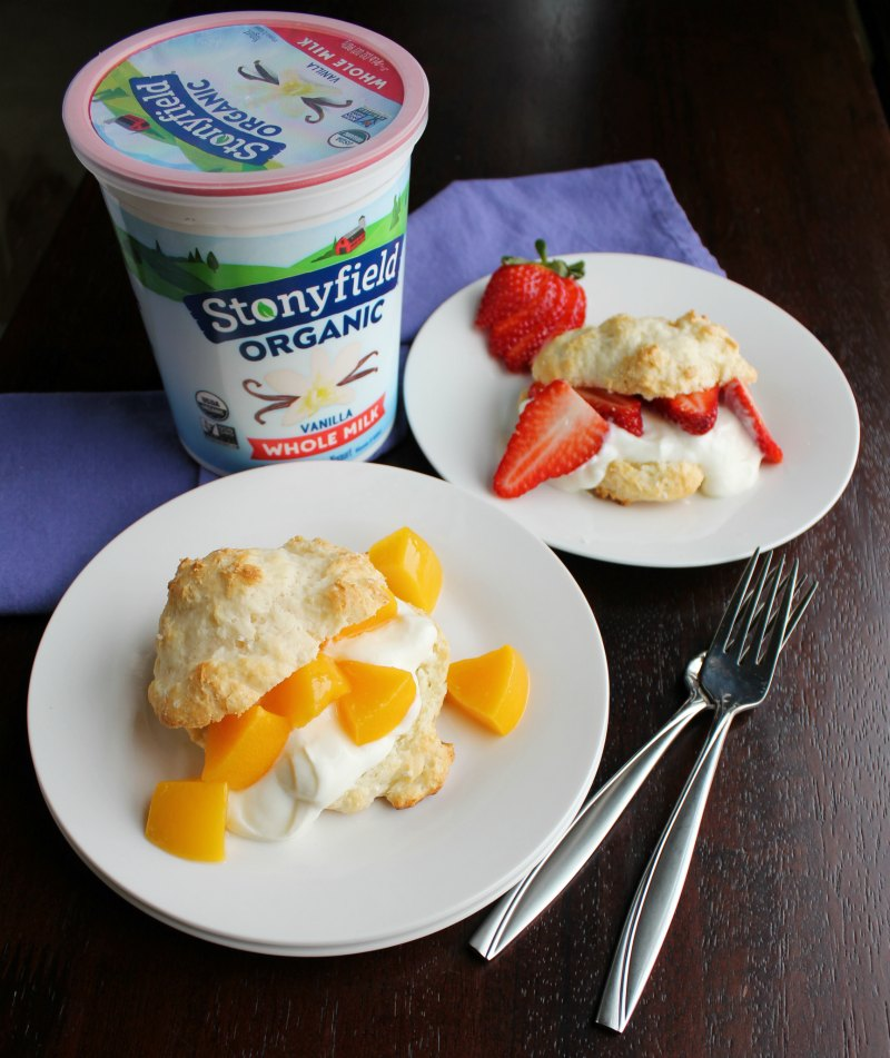 plates of shortcakes filled with yogurt, peaches and strawberries with quart of stonyfield yogurt.