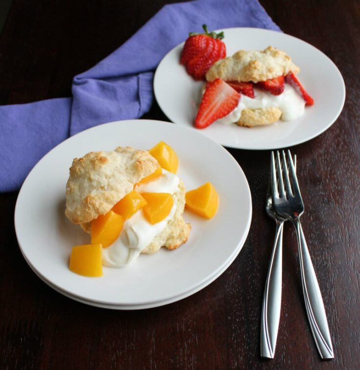 two plates, one with a peach brunch shortcake and one with sliced strawberries and yogurt in a biscuit.