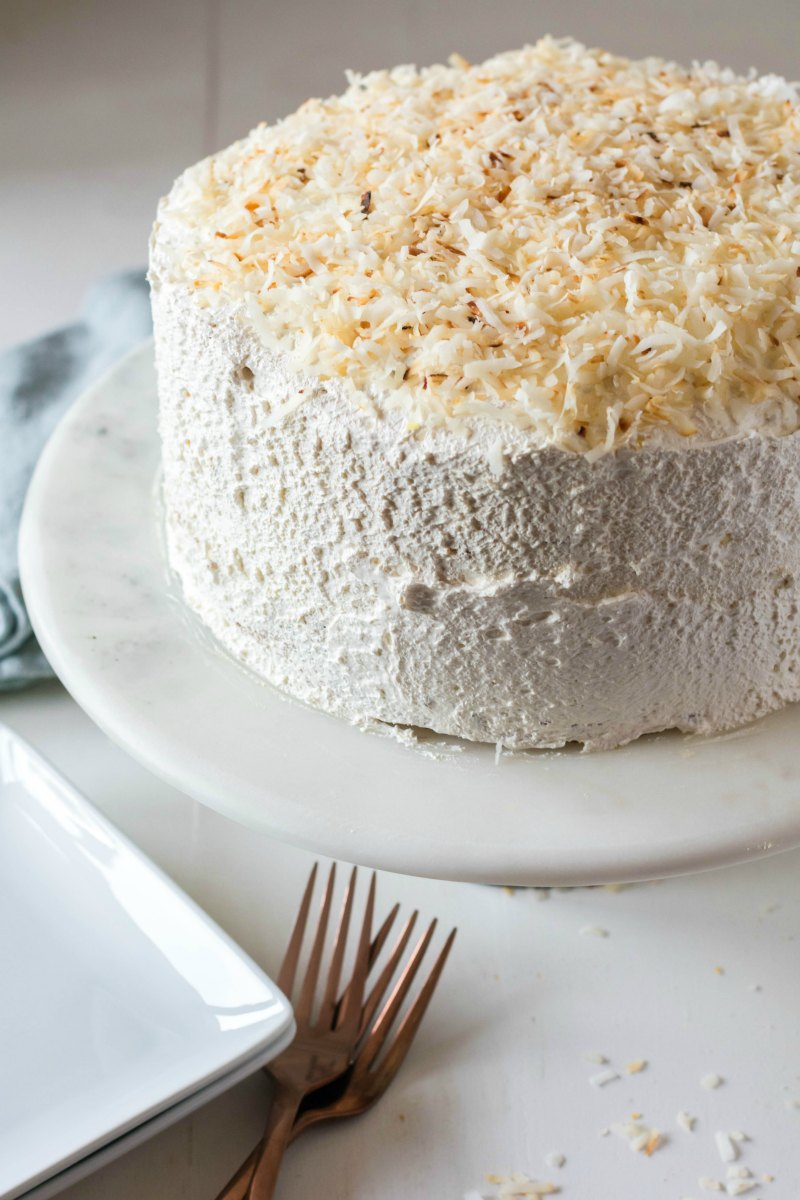 whole haleakala cake with toasted coconut and pineapple with forks and serving plates.