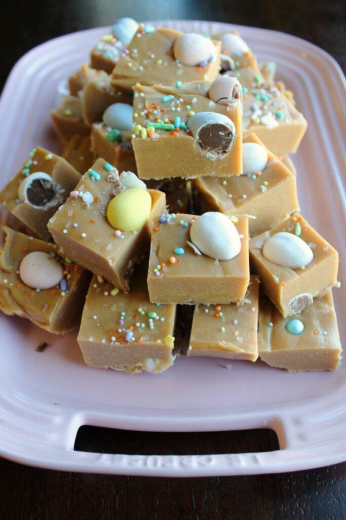 stack of mini egg peanut butter fudge squares on pink platter.