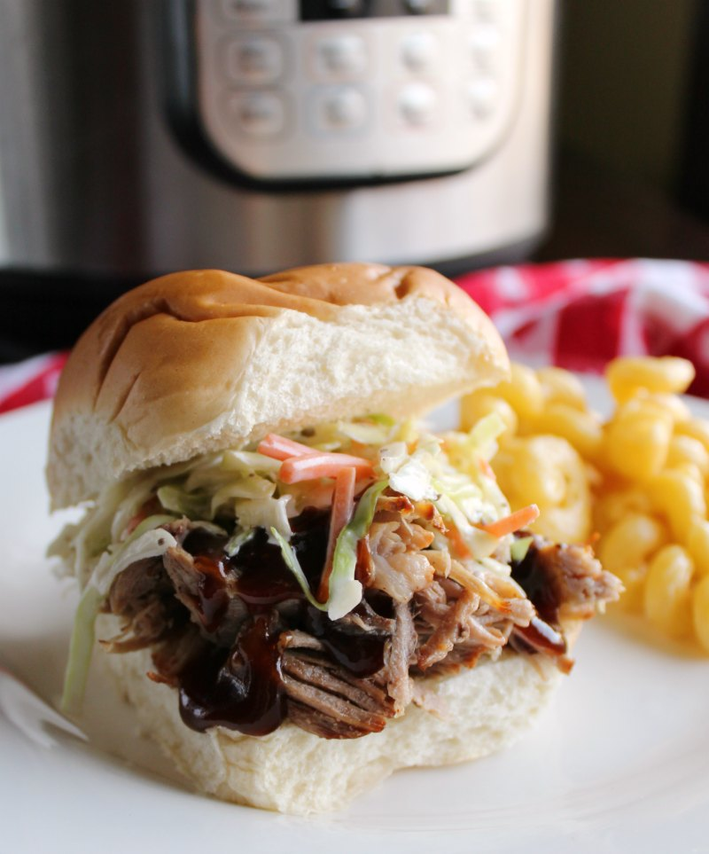pulled pork on bun with macaroni and cheese and instant pot in background.