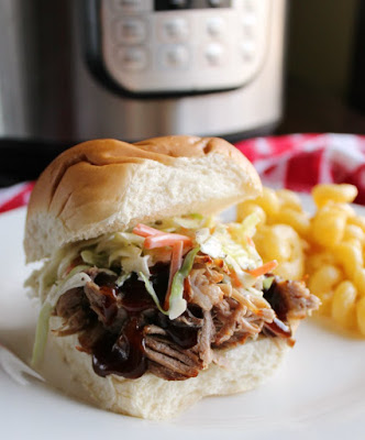 root beer pulled pork sandwich with creamy coleslaw on top in front of instant pot