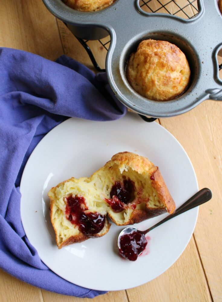 Inside of white cheddar popover with spoonful of raspberry preserves.