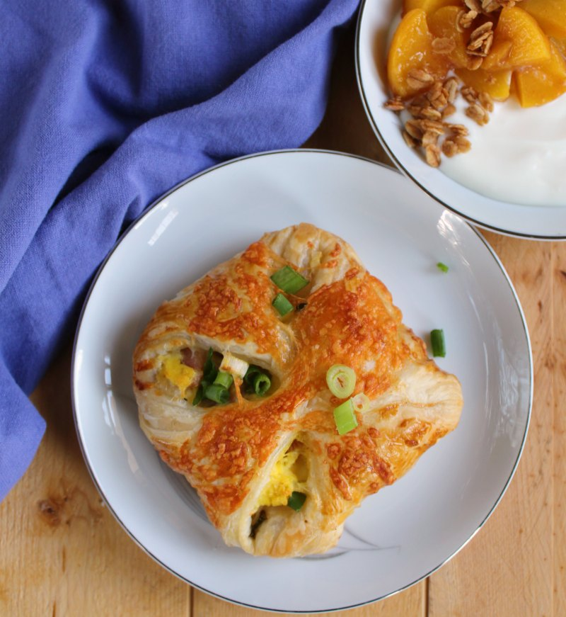 ham egg and cheese hand pie with scallions on top and a bowl of yogurt with peaches and granola in the background.