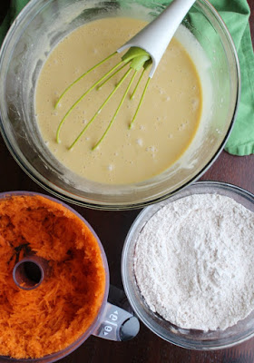 bowls of wet and dry ingredients for carrot cake and food processor with shredded carrots