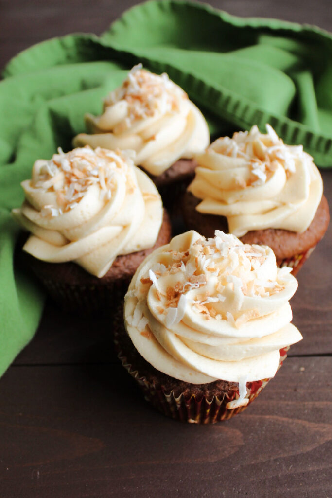 chocolate cupcakes with swirls of caramel buttercream and toasted coconut on top.