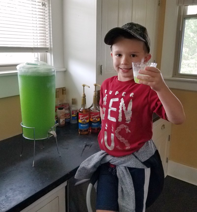 Little dude proudly showing off the first glass of green slime from the dispenser.