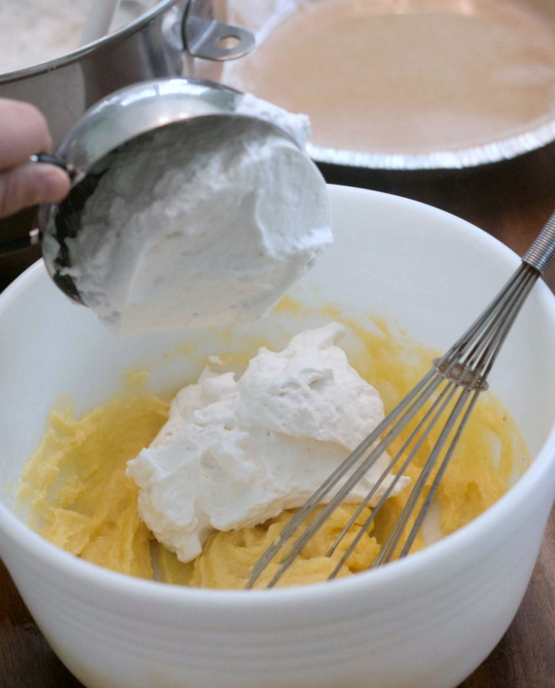 Putting whipped cream into a mixing bowl with pudding mixture.