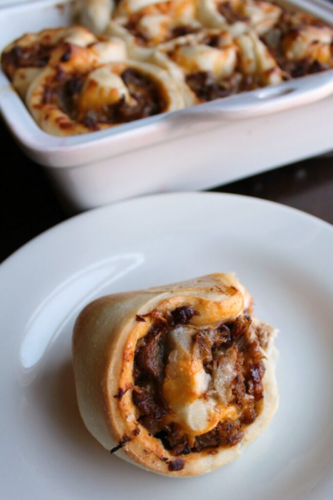 bbq pork and cheese stuffed roll on plate with pan in the background.