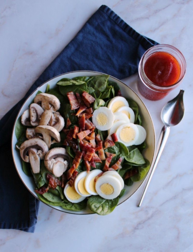 bowl of spinach salad with eggs, bacon, mushrooms and homemade dressing.