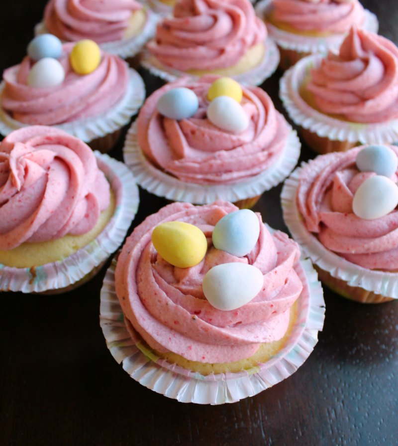 cupcakes with swirls of strawberry buttercream and mini chocolate eggs on top.