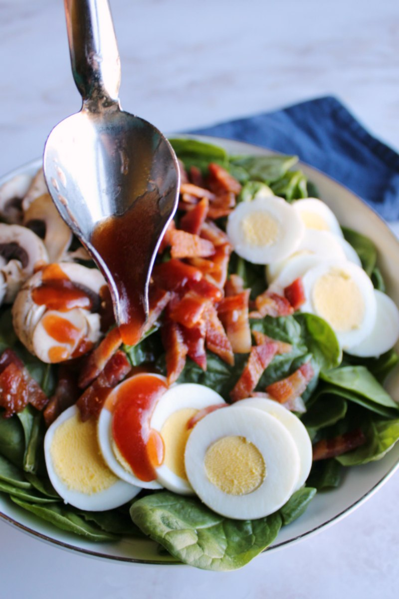 drizzle spoon drizzling red dressing over bowl of spinach salad with eggs bacon and mushrooms.