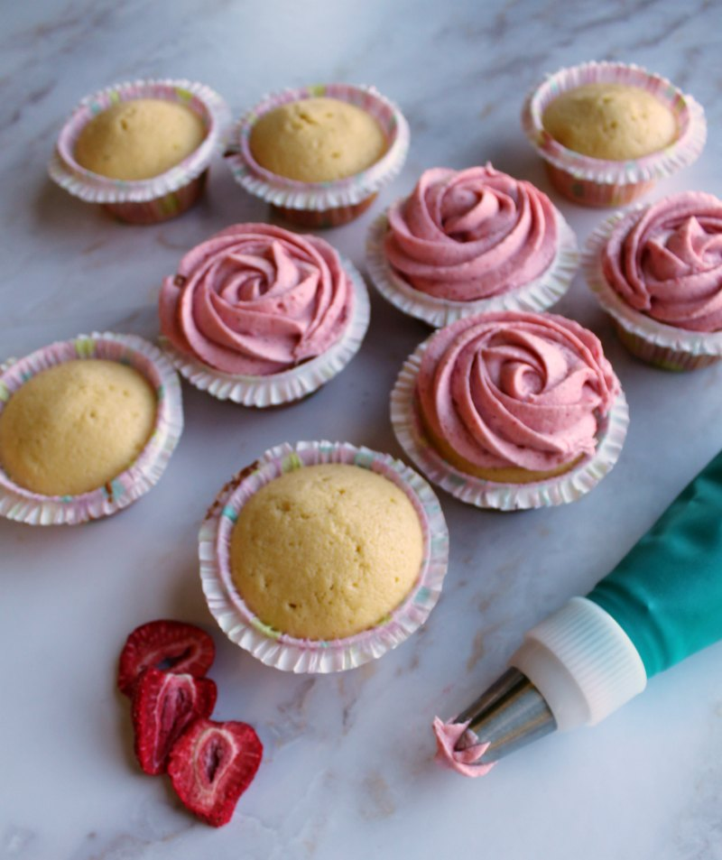vanilla cupcakes getting strawberry buttercream piped on.