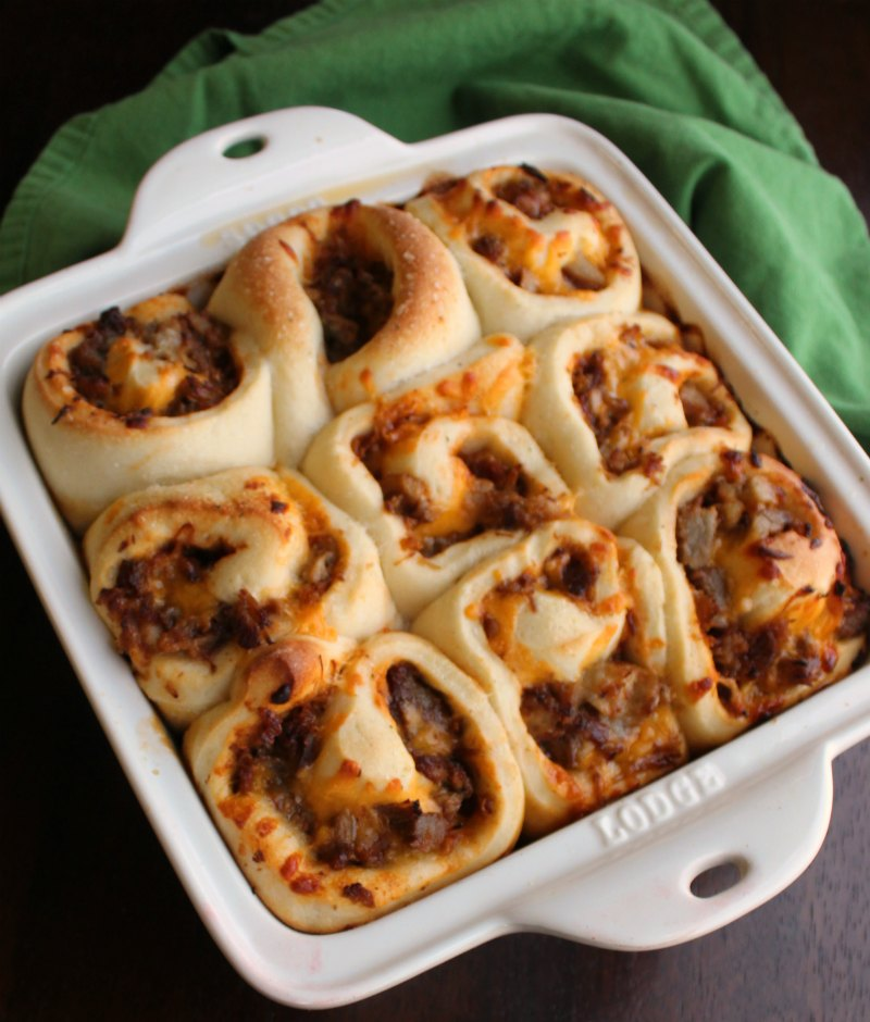 square pan full of golden cinnamon roll shaped rolls stuffed with cheesy bbq pulled pork
