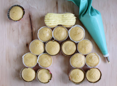 starting to ice the beehive cupcakes with lemon honey frosting
