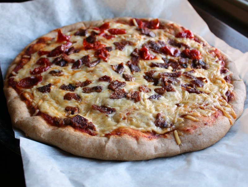 a bacon and red pepper pizza made on whole wheat pizza crust.