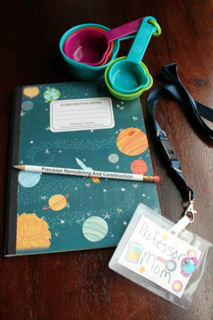 a composition notebook, pencil, name tag and measuring cup for the science kits. not pictured: safety glasses.