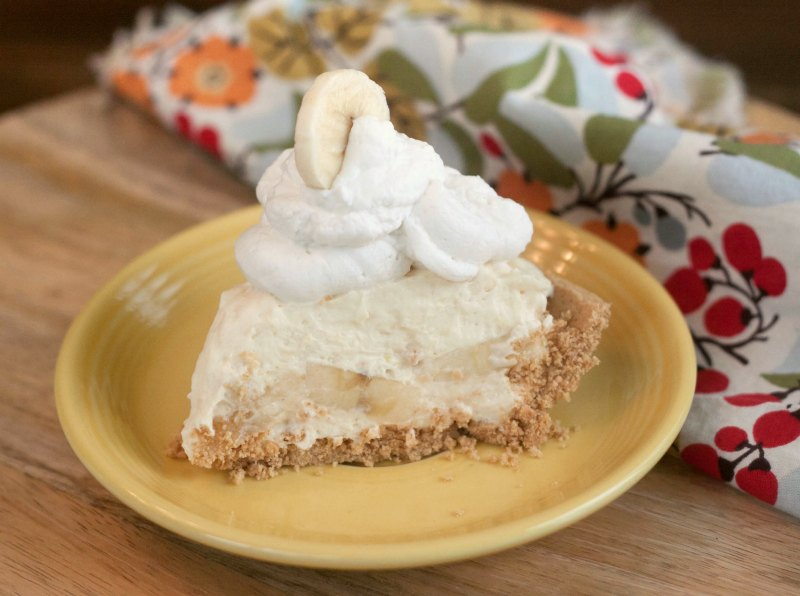 Slice of creamy no cook banana cream pie with graham cracker crust and real whipped cream topping, ready to eat.