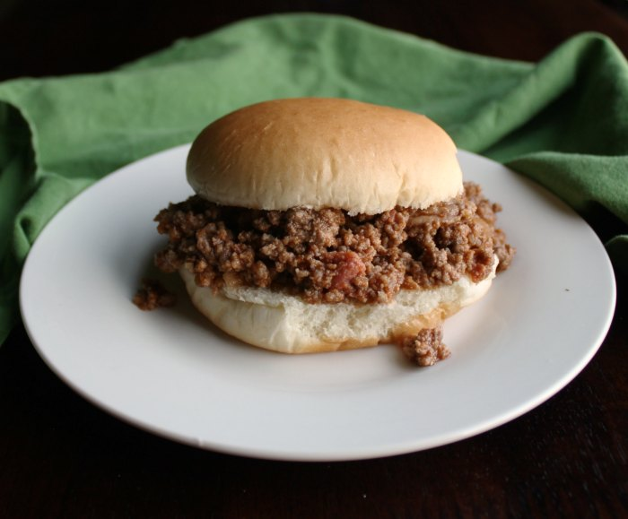 Crumbled sloppy joe meat with tomato sauce on bun, ready to eat.