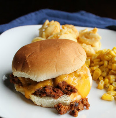 sloppy joe sandwich with melted cheddar cheese on it, macaroni and cheese and corn in the background