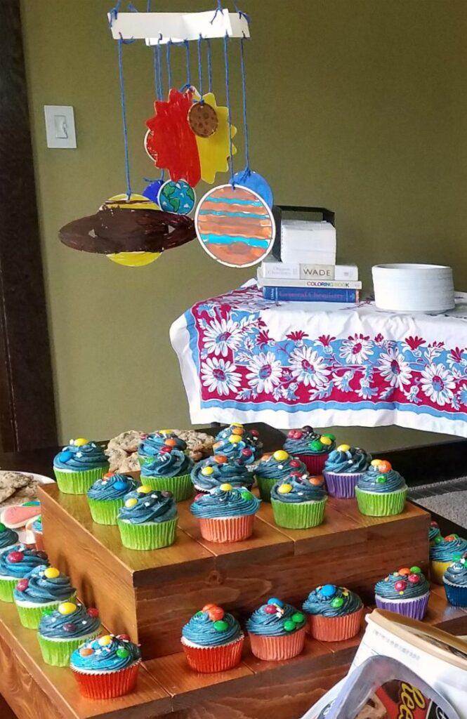 solar system cupcakes on cupcake stand boxes with colored planets mobile hanging above it.