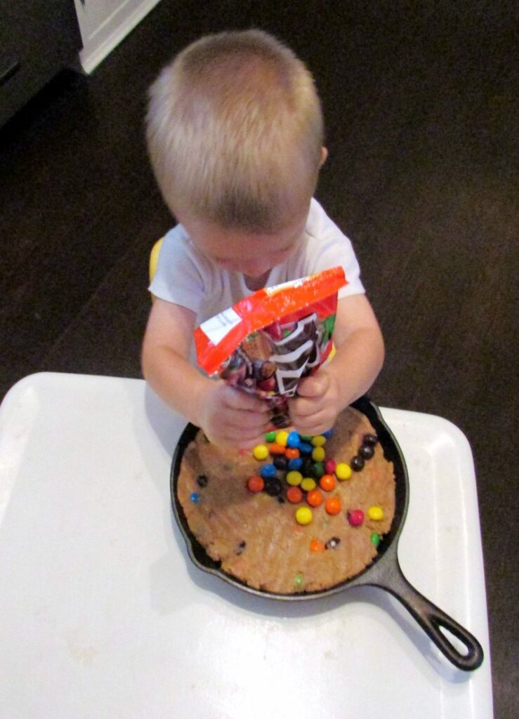 Little dude pouring extra m&ms on top of skillet cookie.