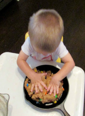 little dude pressing cookie dough into cast iron skillet