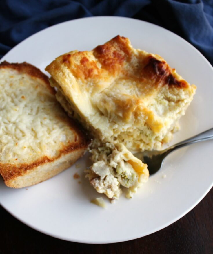 plate with white chicken and broccoli lasagna and piece of garlic bread