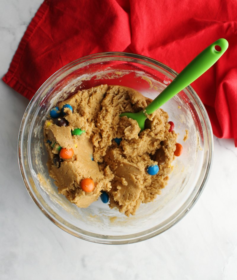 Mixing bowl full of peanut butter cookie dough and peanut butter m&ms.