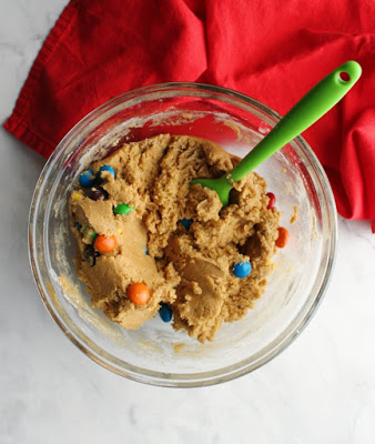 Mixing bowl full of peanut butter cookie dough and peanut butter m&ms